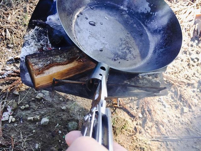 焚き火フライパンをレザーマンで抑える